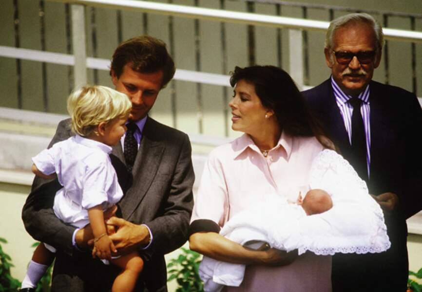Andrea dans les bras de son père regarde la petite Charlotte dans les bras de sa maman Caroline