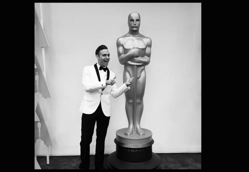Matthew Rodrigues posant à côté de la Statue « oversize » des Oscars