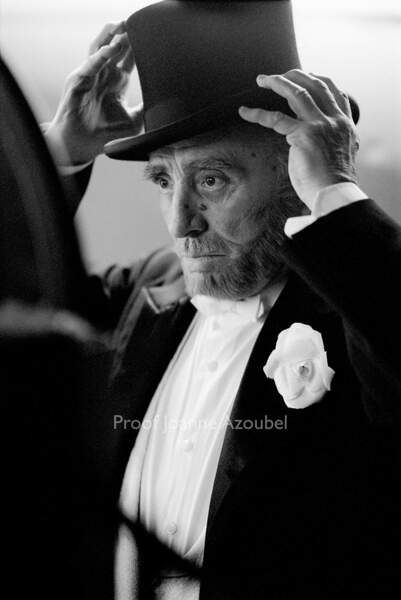 Claude Brasseur ajuste son chapeau dans un miroir placé derrière le rideau, comme un dernier rituel