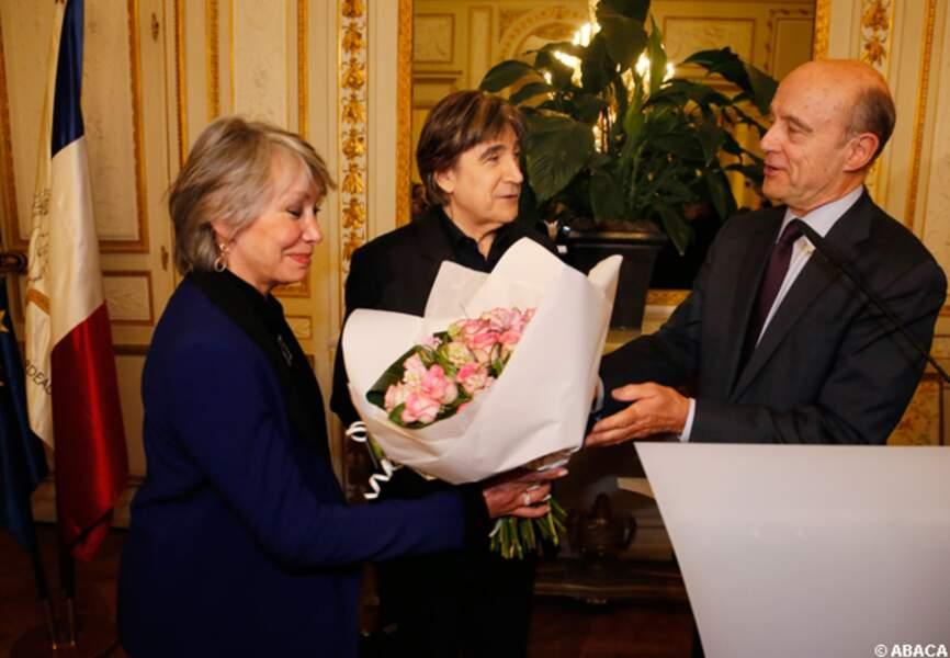 Alain Juppé remet un bouquet de fleurs à la femme de Serge Lama