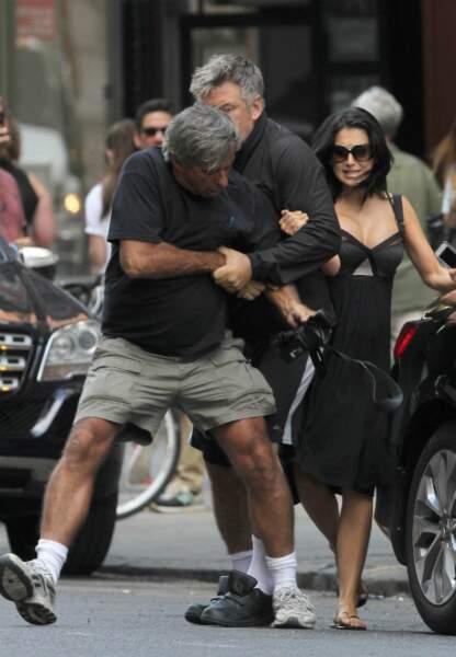 Alec Baldwin agresse un paparazzi. En arrière-plan, Hilaria Thomas, sa femme.