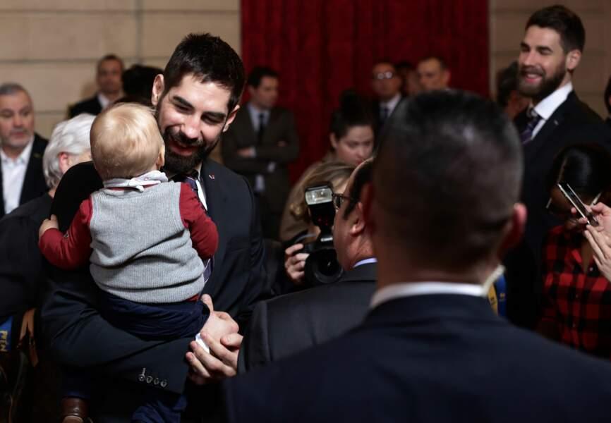 Nicolas Karabatic tient son fils Alek dans les bras.