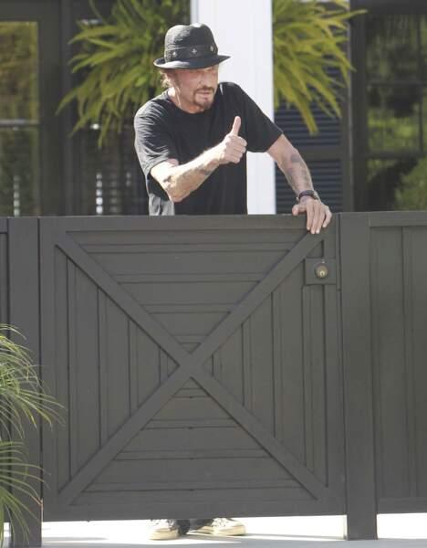Johnny Hallyday salue les photographes devant sa villa de Pacific Palisades, en septembre 2012