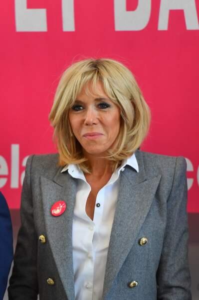Brigitte Macron, chemise blanche ouverte et blazer gris pour sa dictée