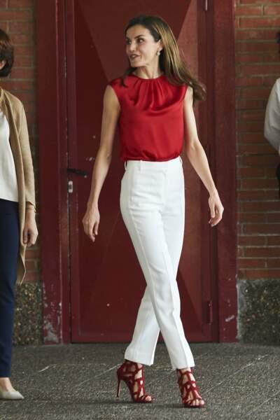 Caliente dans son top en soie rouge, et son pantalon blanc moulant