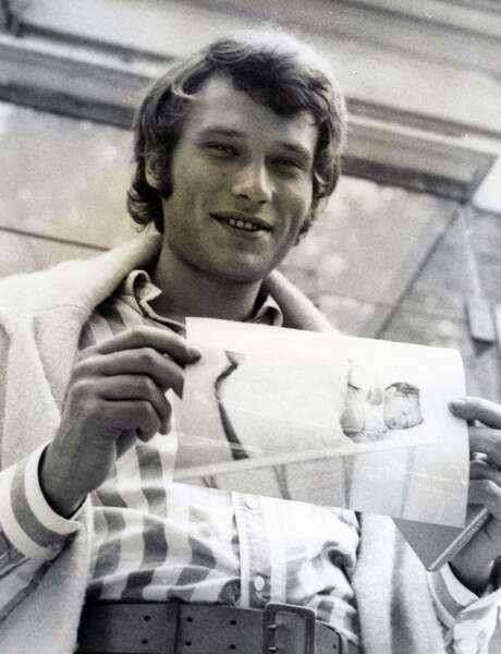 Johnny Hallyday montrant la photo de son fils David, nouveau né, à la sortie de la clinique, le 15 août 1966