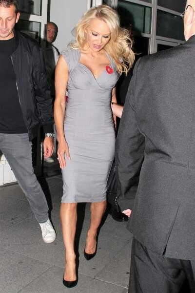 Pamela Anderson chic et sexy en robe grise moulante au décolleté profond