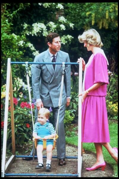 William fait de la balançoire entouré du prince Charles et de Lady Diana, dans les jardins de Kensington en 1984
