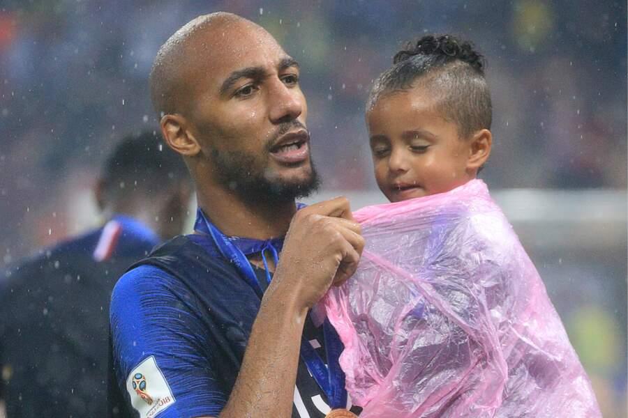Steven Nzonzi protège tant bien que mal sa fille de la pluie, après la victoire des Bleus à la Coupe du monde