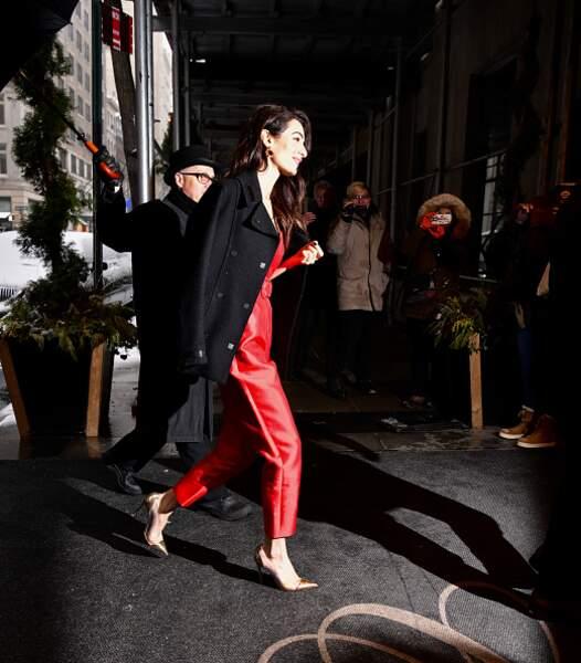 Amal Clooney  associe sa combinaison rouge à un caban chic et une paire d'escarpins dorés