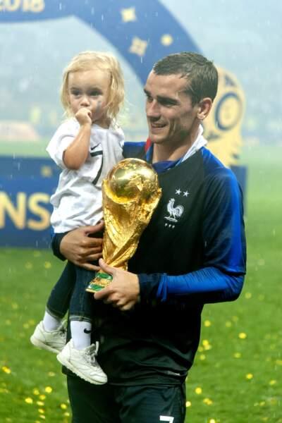 Antoine Griezmann avec la Coupe du monde dans une main et sa fille Mia dans l'autre