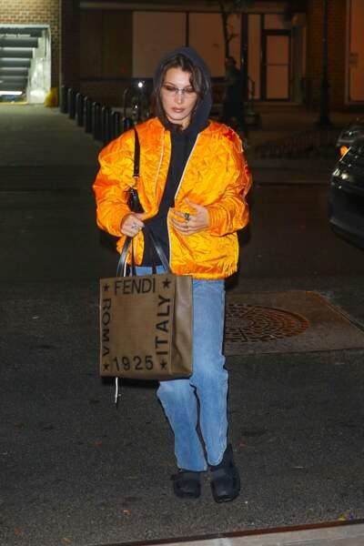Bella Hadid nous inspire un look streetwear : sweat à capuche sur bomber flashy.