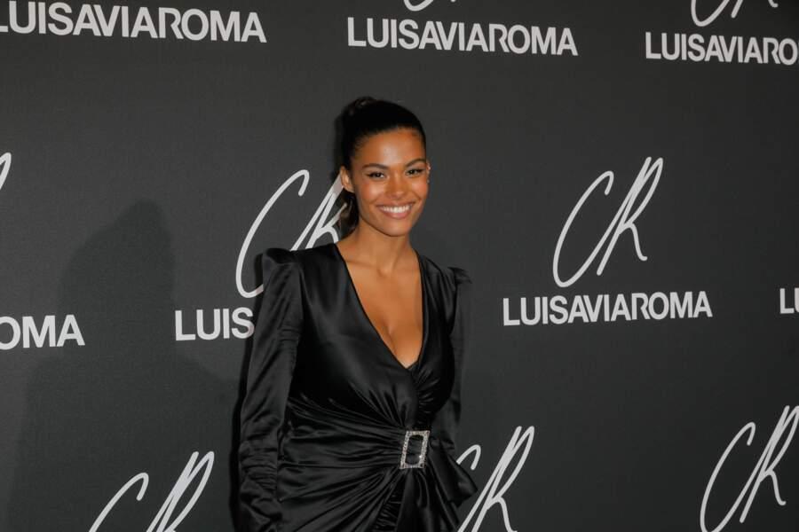 Tina Kunakey Cassel souriante en robe décolletée et trait de liner félin