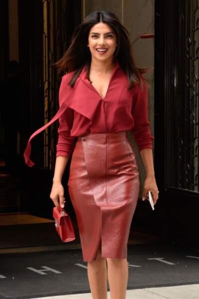 Priyanka Chopra très souriante à la sortie de son appartement à New York en jupe en cuir rouge.