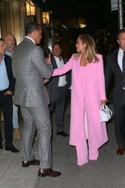 En plus de son costume rose flashy, Jennifer Lopez arborait un mini sac blanc