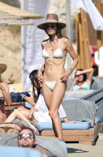 Alessandra Ambrosio joue les naïades en bikini et chapeau de paille.