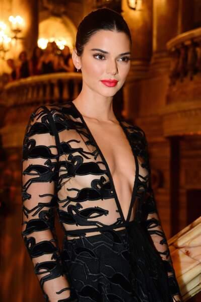 Make-up épuré, bouche rouge et chignon sage, la mise en beauté de Kendall Jenner adoucit sa robe Longchamp.