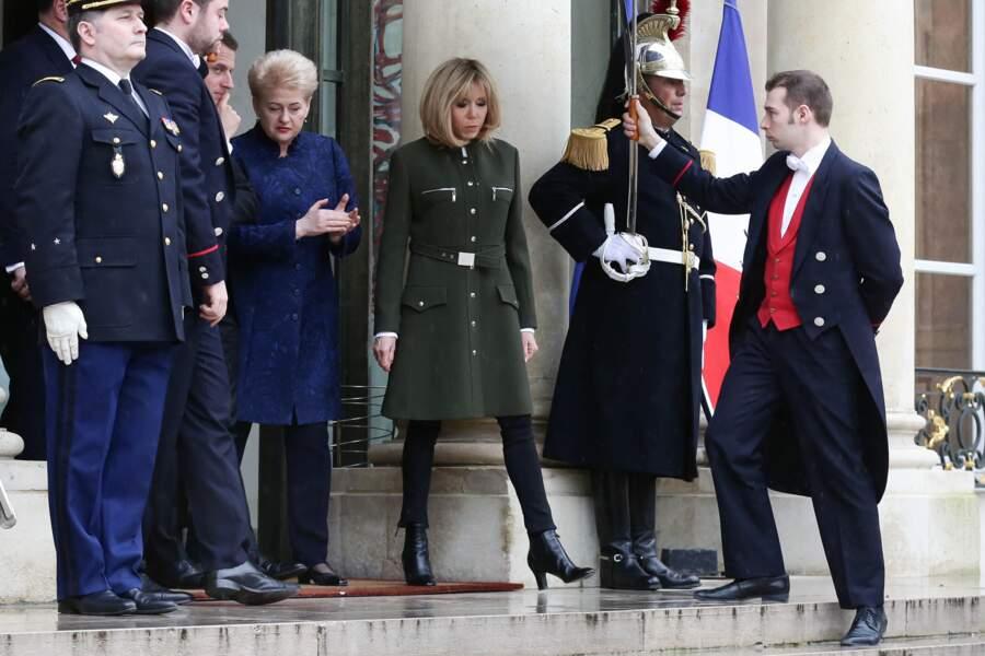 Brigitte Macron en manteau d'officier Louis Vuitton doté de zip, de boutons et ceinturé