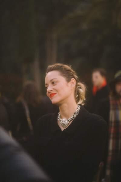 Marion Cotillard, lèvres orange, collier raz-de-cou et veste en tweed au défilé Chanel Haute Couture.