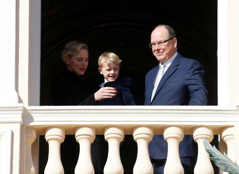 Jacques tout sourire au balcon aux côtés de ses parents