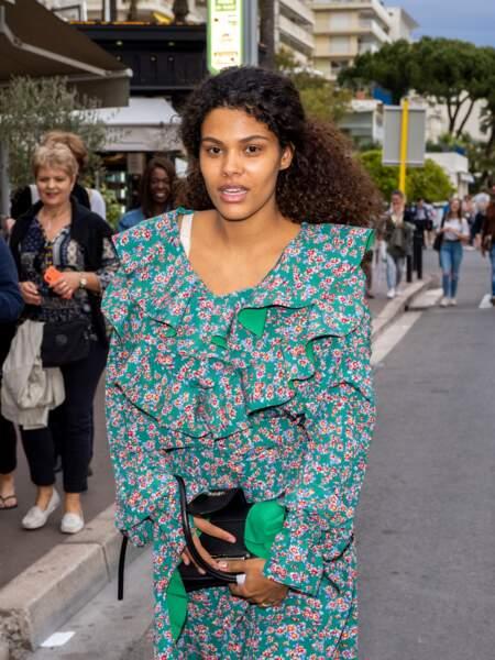 Tina Kunakey en robe fleurie et cheveux noués en queue-de-cheval dans les rues de Cannes