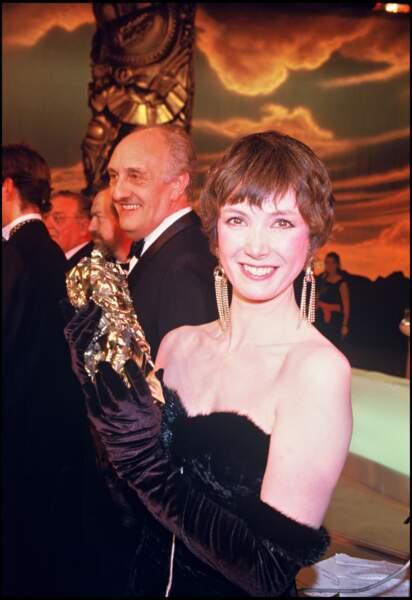 """Sabine Azéma, en robe fourreau bustier pose avec son césar pour """"Un Dimanche à la Campagne"""", en 1985"""