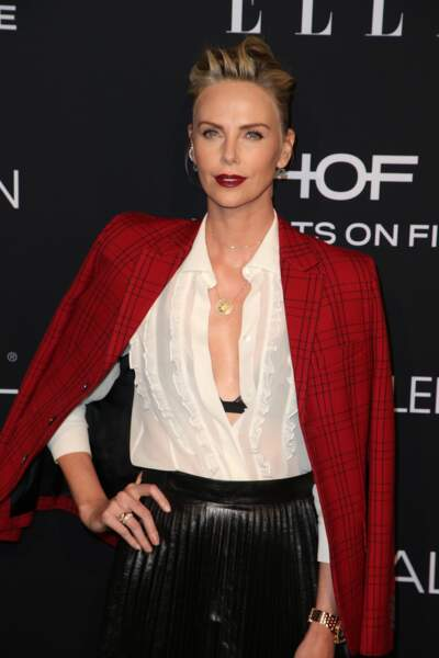 Charlize Theron sexy en rouge carmin avec un chignon aux mèches folles