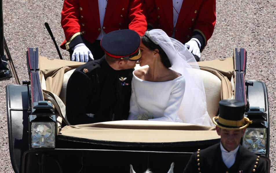 Harry et Meghan échange un baiser, dans la calèche à la sortie du château de Windsor le 19 mai 2018
