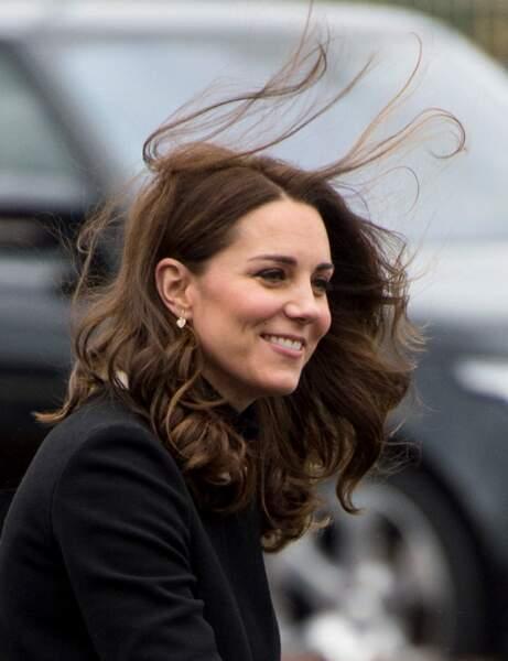 Très souriante, Kate Middleton, les cheveux au vent et des boucles d'oreille en forme de cœur