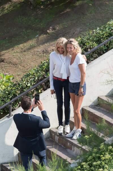 Brigitte Macron prend la pose en jean bleu, blouse blanche et baskets blanches et ceinture rouge = un look à 2665 £