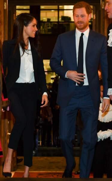Meghan Markle, en tailleur pantalon noir Alexander McQueen, avec le Prince Harry à Londres en février 2018