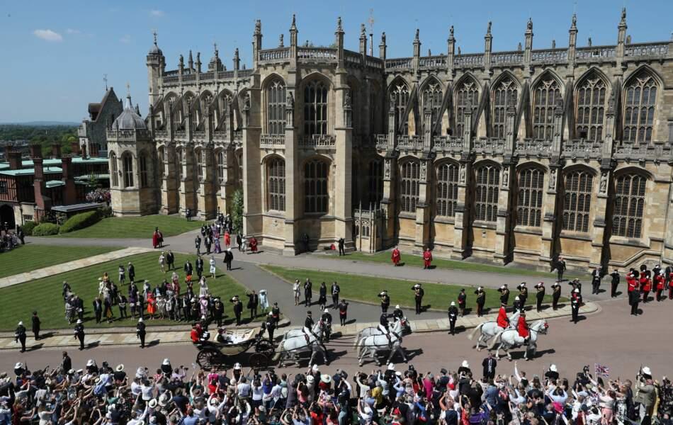 La foule regarde passer le couple royal devant le château de Windsor.
