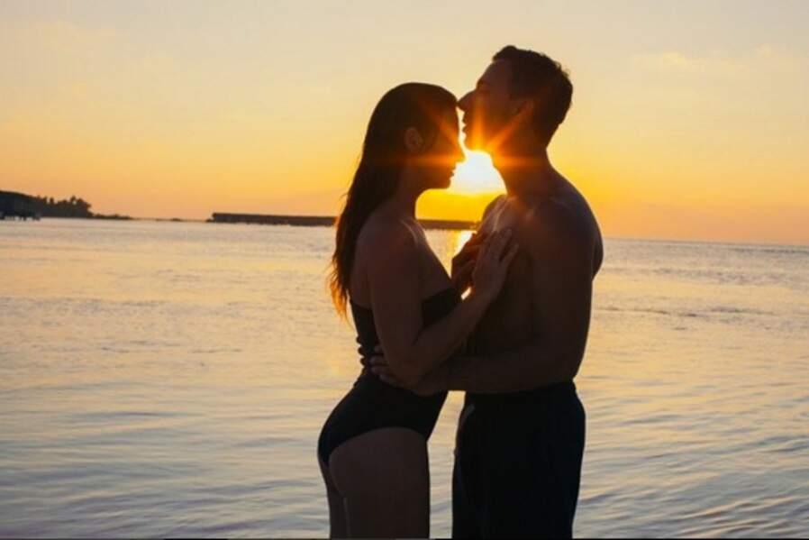 Photo romantique, les amoureux en contre-jour s'échangent de tendres baisers