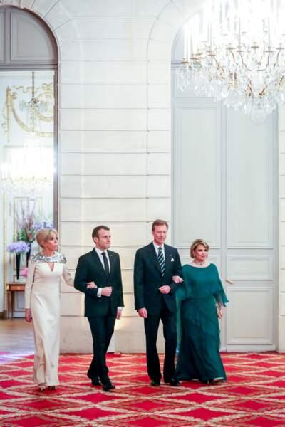 Brigitte Macron en robe longue blanc crème à sequins et son joli chignon sophistiqué