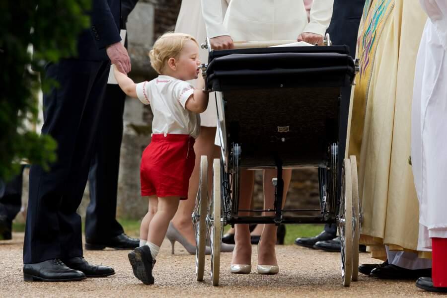 Le prince George observe sa petite soeur, Charlotte, lors de son baptême à Sandringham le 5 juillet 2015