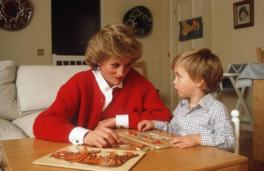 La princesse Lady Diana joue au puzzle avec son fils William dans le palais de Kensington à Londres, en 1985