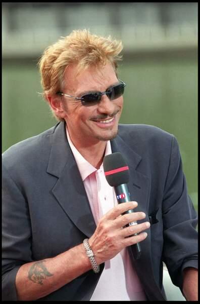 Johnny Hallyday, sur un plateau télé en 2001. Sur son avant bras, une tête de lion, le signe astrologique de David