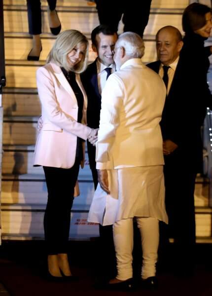 Brigitte Macron, très sophistiqué à son arrivée en Inde, en escarpins et pantalons noir et veste rose pâle en satin