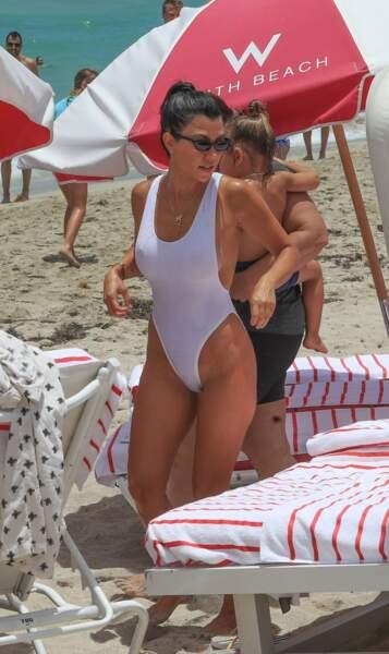 Kourtney Kardashian ne jure plus que par le maillot une pièce blanc.