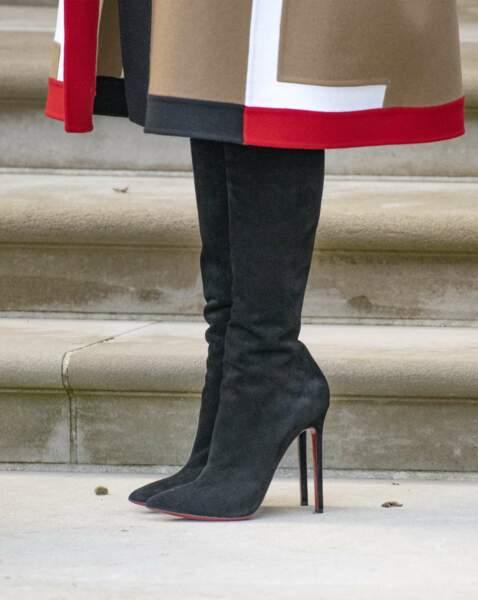 Un manteau à motifs géométriques porté avec des bottes noires à talon aiguill