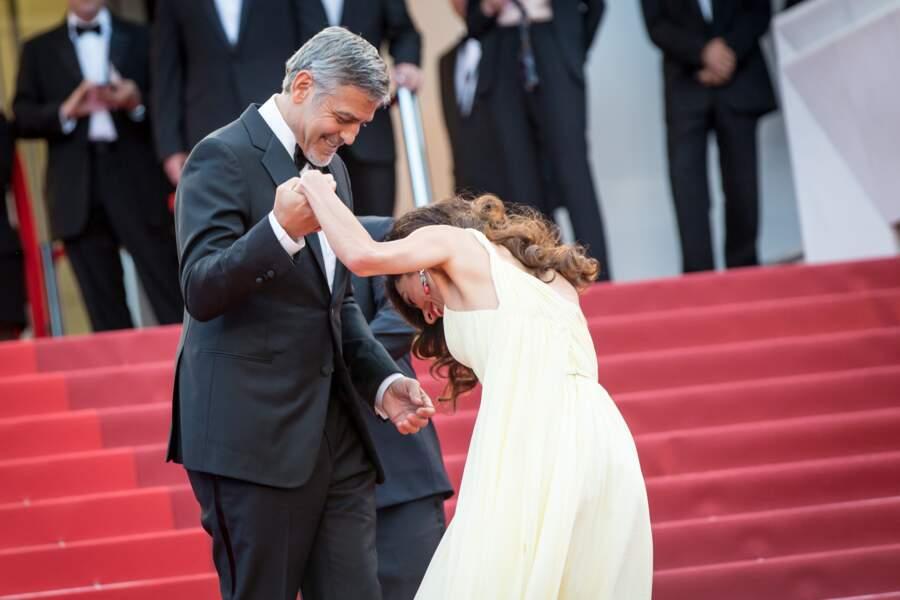 Amal Clooney trébuche dans sa robe, mais est sauvée par son mari George à Cannes en 2016