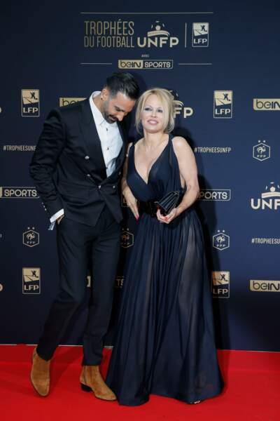 Adil Rami portait un blazer noir et des boots Balmain, Pamela Anderson était habillée de mousseline noire