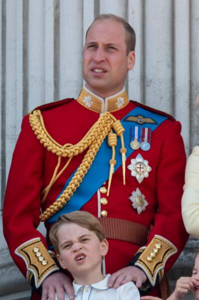 Le Prince William impressionant en costume militaire rouge avec son fils le prince George