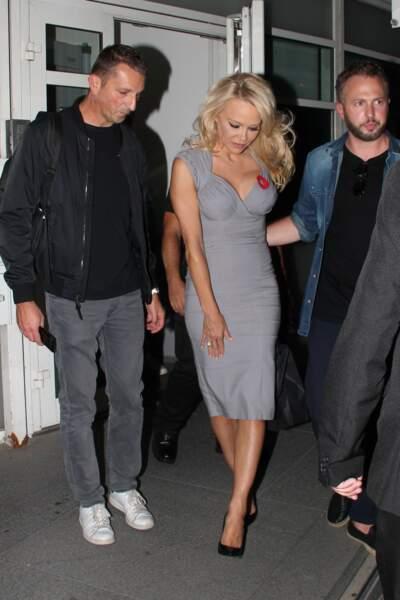 Pamela Anderson en robe grise longue sous le genou et une paire d'escarpins Saint-Laurent