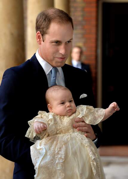 Le prince George dans les bras de son père William d'Angleterre lors de son baptême, le 23 octobre 2013 à Londres