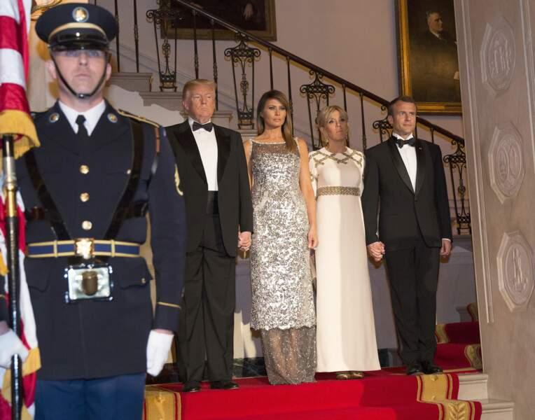Brigitte Macron en robe de vestale blanche et dorée Louis Vuitton avec Melania Trump le 24 avril 2018