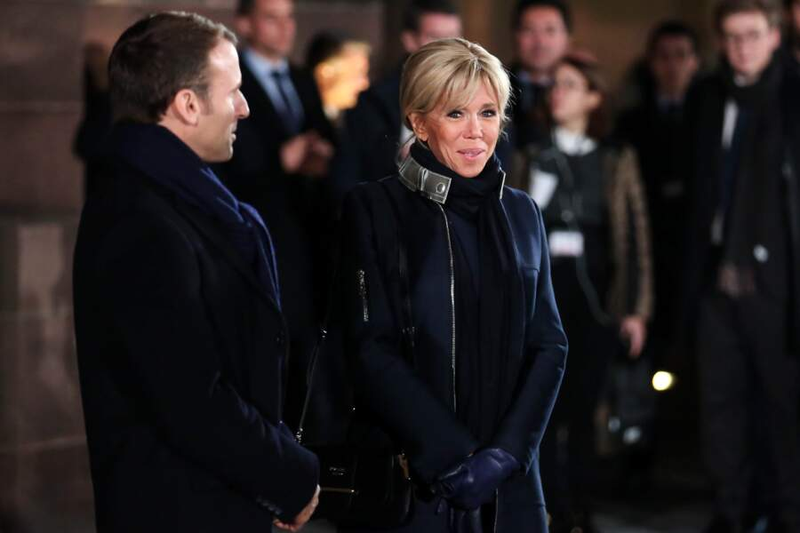Le manteau bleu marine aux liserés argentés de Brigitte Macron est signé Louis Vuitton.
