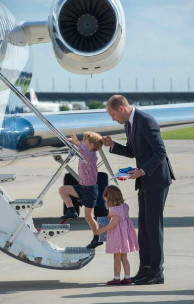 Le Prince William aidant ses enfants à monter dans l'avion