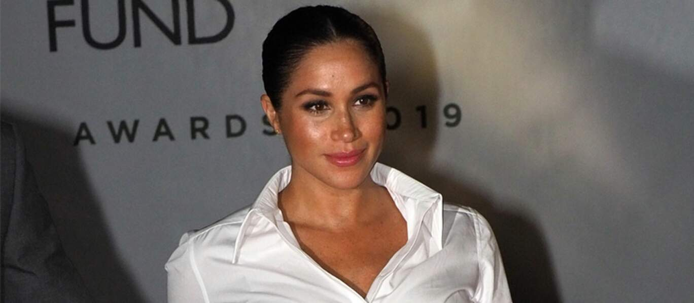Meghan Markle est apparue dans une tenue de working girl, avec une jupe fendue et une chemise ouverte.