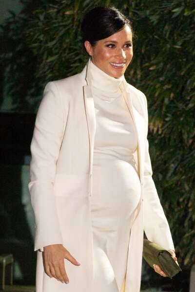 Meghan Markle dont le teint et les cheveux sont mis en valeur par le choix de sa tenue claire